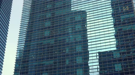 singapur : Reflecting Glass Facade of Two Modern Office Skyscrapers - Panning From Right To Left Stok Video