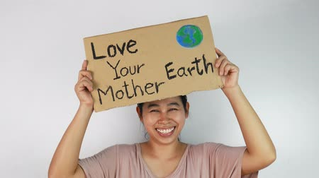 sos : Woman holding Love your Mother Earth Poster on a demonstration due to climate change by plastic pollution. Stok Video