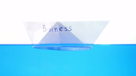 Folded paper boat floating on the water surface. Business issues concept. 動画素材