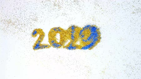 New year 2019 change to 2020 concept, The wind blew blue  glittery glitter from 2019 to 2020 yellow glitter, isolated on white background. 動画素材