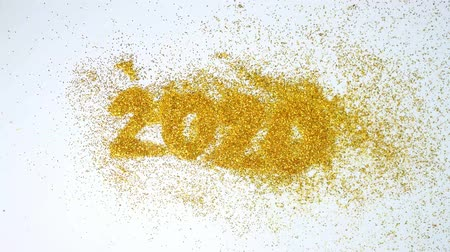 New Year 2020 is coming concept, The wind blew yellow glittery glitter show 2020 isolated on white background.