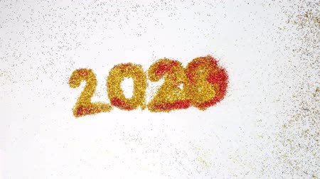 запомнить : New year 2019 change to 2020 concept, The wind blew red glittery glitter from 2019 to 2020 yellow glitter, isolated on white background.