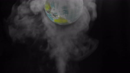 salva vidas : The simulated earth spins above steam smoke that shot up on a black background. Concept of earth destroyed by pollution.