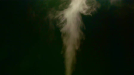 Close up of yellow steam smoke shot up on a black background. Concept of abstract backdrop.