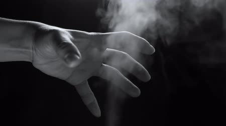 salva vidas : Hand in steam smoke shot up on a black background. Vídeos