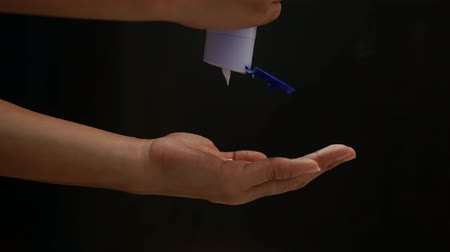 squeeze : Womans Hand pouring body care lotion from bottle into her hand isolated on black background. Skin care concept.