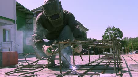 kaynakçı : a worker at a construction site conducts welding work on a summer day; close-up of a cypispase
