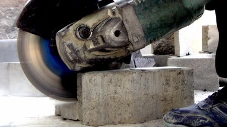 equipamento : A worker at a construction site cuts off a paving slab with an angle grinder. Dust flies.