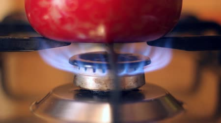 gas hob : a red pan stands on the gas burner of the stove under which gas burns with blue fire Stock Footage