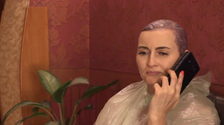 щеткой : beautiful young woman in a hairdresser with dyed hair sitting in the lobby and talking on a cell phone Стоковые видеозаписи