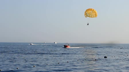 padák : on a sunny day a motor boat pulls a parachute at sea, parasailing