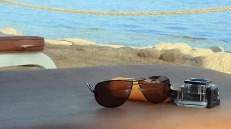 kompakt : on a table by the sea on a sunny summer day are sunglasses and a camera for underwater shooting Stok Video