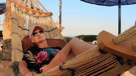 hamak : on a sunny summer day, a beautiful young woman in a sun cap and black sunglasses rests in a hammock on the seashore in the shade of palm trees Dostupné videozáznamy