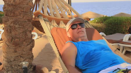 odstín : On the shore of the Red Sea in Egypt, a young man in a black cap and sunglasses from the sun rests in a hammock on a sunny summer day in the shade of palm trees Dostupné videozáznamy