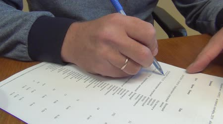 el yazısı : checking a finished document and reading it, a man makes corrections in the entries on a sheet of white paper with a blue ink ballpoint pen, close-up Stok Video