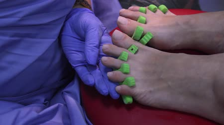 aplikatör : Woman having a manicure of nails in a beauty salon with a closeup view of a beautician applying nail polish with an applicator. The master painted his nails with varnish. Details shot of hands applying a red nail. Stok Video