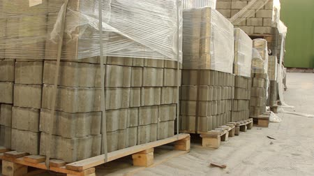 スラブ : pan shot of stacks of paving stones wrapped in construction film stored outdoors