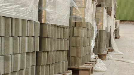 pan shot of stacks of paving stones wrapped in construction film stored outdoors