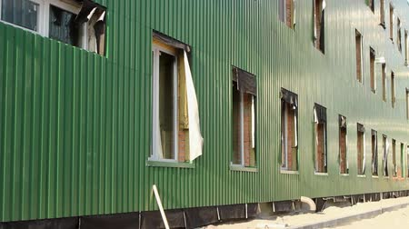 the building under repair is warming the facade and wall cladding with green siding; the wind develops insulation