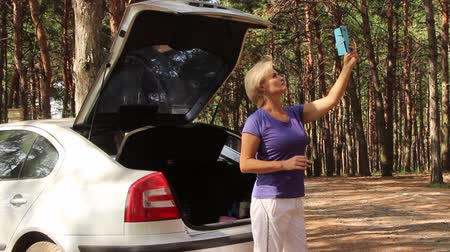 A woman in the forest is trying to catch, looking for a signal on a mobile phone in the forest, standing near a stopped car with the back door open Wideo