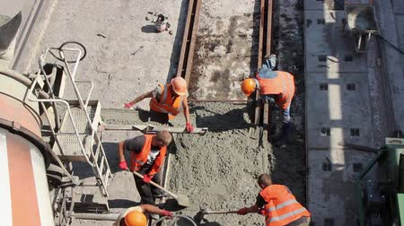 workers pour concrete between rails and sleepers during repair of a lane road, equal with shovels, carry on a wheelbarrow