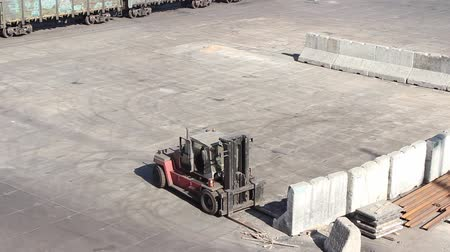 stockpile : loader work on the port berth moves concrete blocks to form bulk cargo boundaries Stock Footage