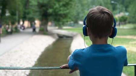 A teenager listens to music on headphones. Child in headphones. Rest in the park. The boy is standing on the bridge. Back view.