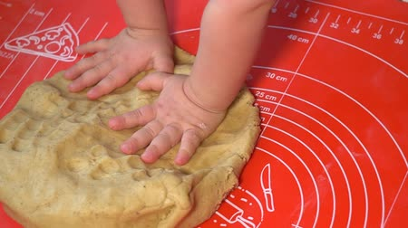 A small child kneaded the dough. Dough on a silicone rug. Making a dough for gingerbread. Slow image.