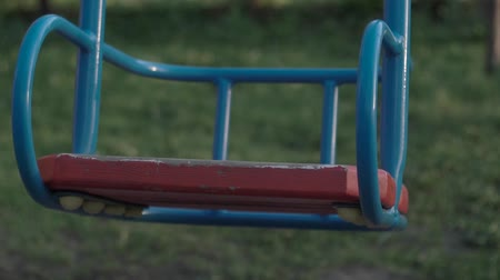 Playground. Empty oscillations. City Park. Slow shooting. Childrens swing move slowly Stok Video
