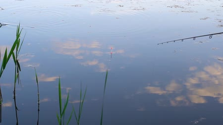 Fishing on the river. Beautiful lake surface. Reflection of clouds on the water surface. Fishing rod. The blue sky is reflected in the lake. White clouds are reflected in the water.