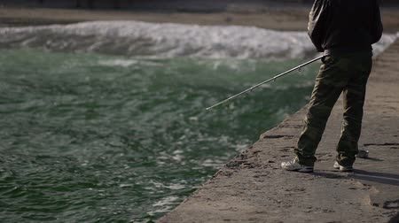 The man is fishing. Sport fishing. Black Sea. Fishing with spinning. Fishing on the coast in the fall. Stok Video