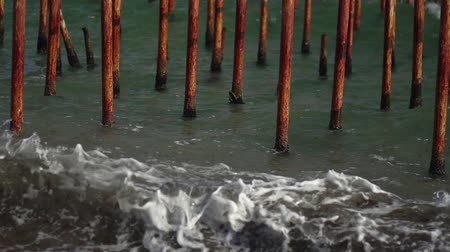 Old rusty pier. Sea waves in slow motion. Rusty iron pier.