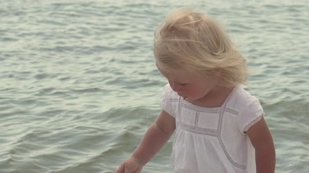 A child by the sea. Little girl in slow motion. Child girl in slow motion on the coast of the tropical sea. Summer vacation by the sea. Beautiful little girl walks along the seashore. Little girl in a white dress on the coast. Slow motion.