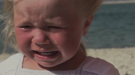 Crying little girl by the sea. Little girl with tears in her eyes. Tears drip from the childs eyes in slow motion. Crying little girl. Nervous disorder in children. Sunburn on the face of the baby. Stok Video