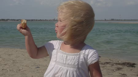 Little girl has breakfast on the beach. A child on the coast. Happy joyful child. Rest on the coast of the southern sea. Little girl in a white dress on the seashore. Cute joyful child. Baby girl with blond hair in the wind. Stok Video