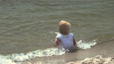 A little girl bathes in the sea. The child sits in the sea. A girl of three years is swimming in sea water. A small child splashing in the water. Young age girl in a beautiful white dress on the beach.