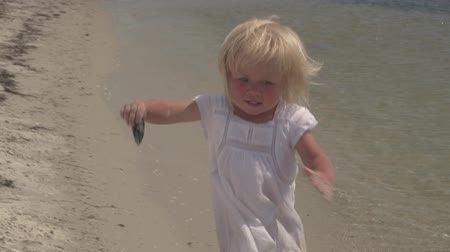 Beautiful little girl runs along the seashore. Laughing baby. Little girl in white dress running on the coast. Slow motion. Joyful running child. A little girl in slow motion runs along the coast. Child girl in slow motion on the coast of the tropical sea Stok Video