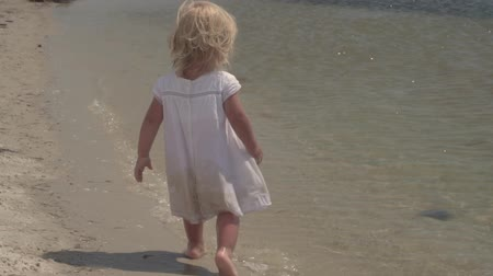Beautiful little girl walks along the seashore. Little girl in a white dress on the coast. Slow motion. A child by the sea. Little girl in slow motion. Child girl in slow motion on the coast of the tropical sea. Summer vacation by the sea.