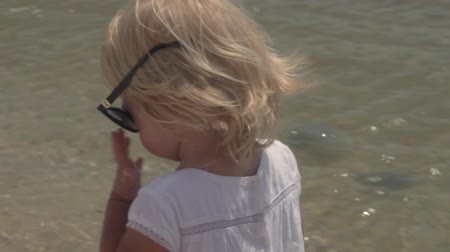Little girl in sunglasses on the coast. Beautiful little girl wears sunglasses. Little girl in a white dress on the coast. Slow motion.