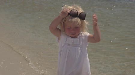 Beautiful little girl wears sunglasses. Little girl in a white dress on the coast. Slow motion. Little girl in sunglasses on the coast. Stok Video