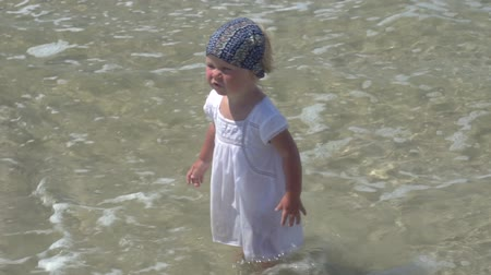 A child is standing in the sea water. Little girl in a white dress walks in the sea water. Alarmed child stands in the sea. Little girl with a scarf on her head. A child on the beach of a tropical island.