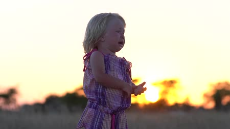 Crying little girl alone in the meadow. Child at sunset in the meadow. Crying baby. Slow motion. Abandoned children. Lost baby. Little saddened girl. Offended child. Little girl with tears on her face.