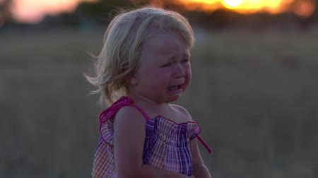 Crying baby. Child at sunset in the meadow. Childrens crying. Crying baby. Slow motion. Abandoned children. Lost baby. Little saddened girl. Offended child. Little girl with tears on her face. Stok Video