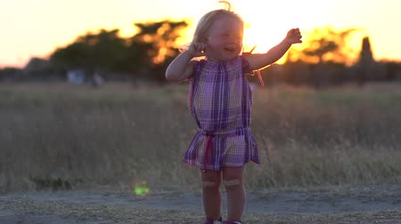 harmonia : A little girl stands in a meadow during sunset. Real childrens feelings. Not fake childrens emotions. Adhesive plaster on a childs lap. Childrens laughter. Slow motion.