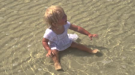Baby by the sea. The child bathes in the sea. Rest on the coast. Joyful child at the sea. Slow motion. Shooting from above.