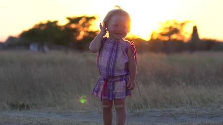 A little girl stands in a meadow during sunset. Real childrens feelings. Not fake childrens emotions. Adhesive plaster on a childs lap. Childrens laughter. Slow motion.