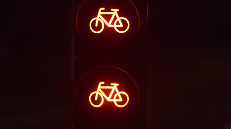Semaphore warning sign. Movement in the night city. Evening street of Luxembourg. Red bicycle traffic warning sign. Stock mozgókép