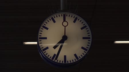 пригородный : Clock at the train station in Luxembourg. The movement of the clock hands. Platform station in the evening. City Station. The clock on the platform of the train station.