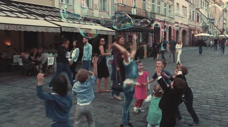Ukraine Lviv May 27, 2016. Joyful children catch soap bubbles.Children run for big soap bubbles. Cheerful children.