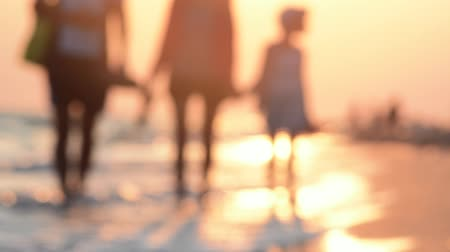 Mom, dad and daughter walk barefoot on the beach. Happy family relationships. Parents and daughter are walking. Summer evening at the resort on the ocean. Young family during the holidays. Out of focus. Summer sunset on the ocean. Stock mozgókép